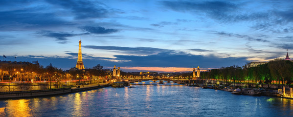 Paris France panorama city skyline night at Seine River with Pont Alexandre III bridge and Eiffel...