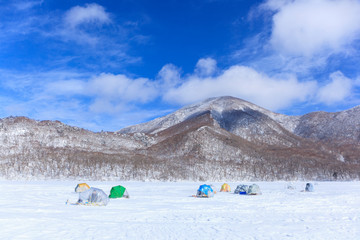 冬の赤城山と氷結した大沼でワカサギ釣り風景 群馬県前橋市