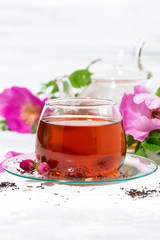 fragrant tea with wild rose in a glass cup on a white background, vertical