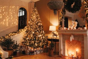 warm cozy evening in Christmas room interior design,Xmas tree decorated by lights gifts,toys, deer,candles, lanterns, garland lighting indoors fireplace.holiday.magic New year