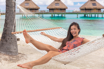 Wall Mural - Beach vacation cheerful young Asian woman relaxing having fun in hammock by tropical luxury overwater bungalow resort.