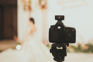 Close-up of professional DSLR digitak camera attached with tripod in wedding ceremony and with bride in wedding dress blurred out in background