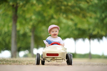 happy little girl in toy car - summer day in park