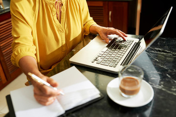 Mature woman sitting at marble table, working on laptop and taking notes in planner