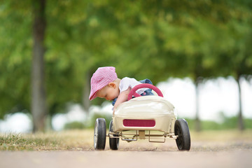 summer day in park - happy little girl in toy car