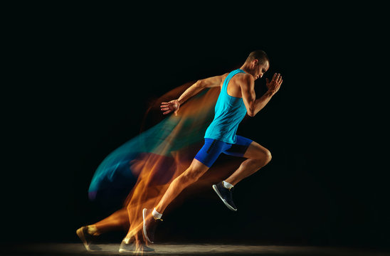Professional male runner training isolated on black studio background in mixed light. Man in sportsuit practicing in run or jogging. Healthy lifestyle, sport, workout, motion and action concept.