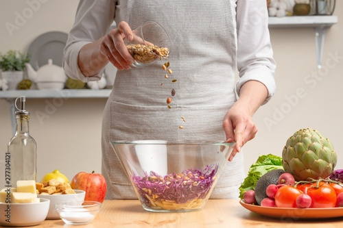 Chef sprinkles salad with nuts, stir, in the process of a