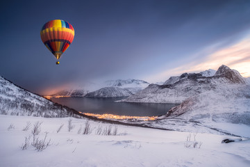 Foto auf AluDibond Ballon Hot air balloon flying on snow hill with fordgard town in winter