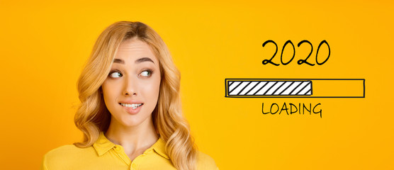 Blonde biting her lip and looking at 2020 loading process Wall mural