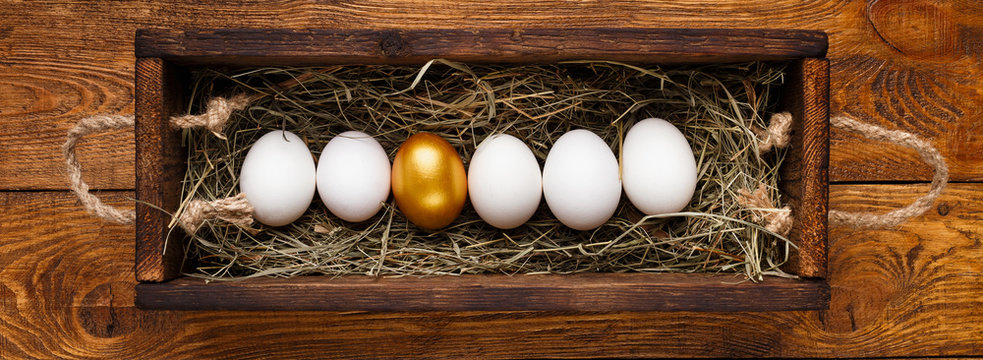 One golden egg among row of white in wooden box