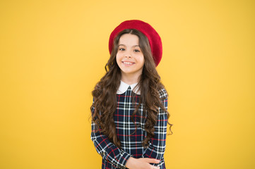small girl kid with long curly hair. fashionable school uniform. kid fashion. parisian fashion girl. childrens day. child on yellow background. happy girl in french beret. Joyful mood