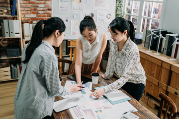 marketing manager woman pointing at business document during discussion at meeting. girl team leader showing employee on data paper on wood table. three ladies colleagues standing in boardroom