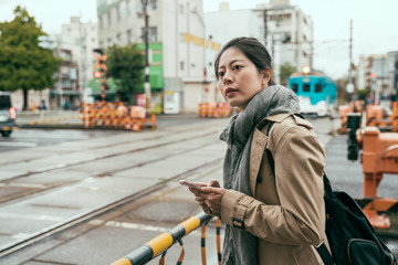 beautiful asian korean woman traveler standing next to crossing railroad to wait train drive through. young girl backpacker travel in osaka city by foot and holding cellphone searching online map.