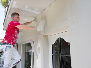 plasterer in red shirt works on white plaster of old house