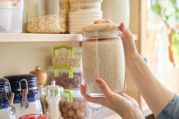Food products in the kitchen. Woman taking jar of rice