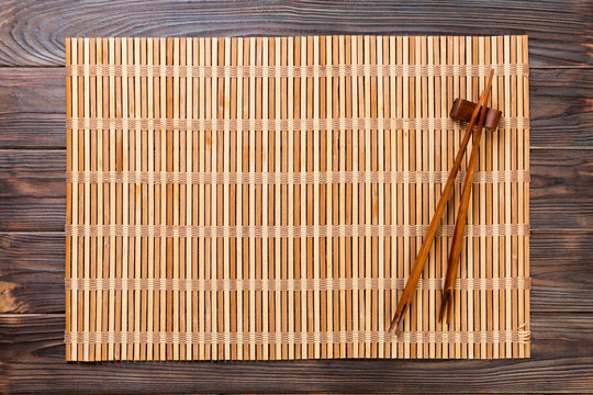 two sushi chopsticks with empty brown bamboo mat or wood plate on wooden Background Top view with copy space. empty asian food background