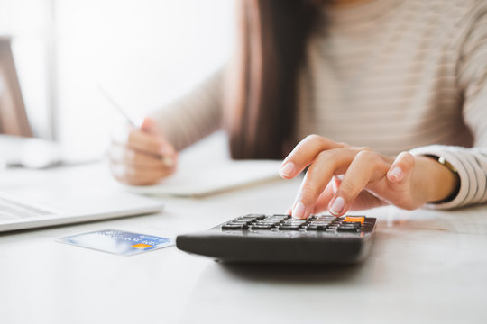 Woman accountant working with computer and calculator for business and financial expense