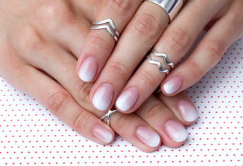 Two hands with manicure at the creative polka dot background.