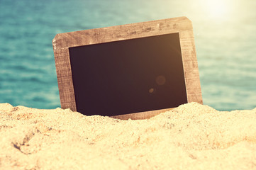 Vintage blank chalkboard in the sand of a beach, summer background