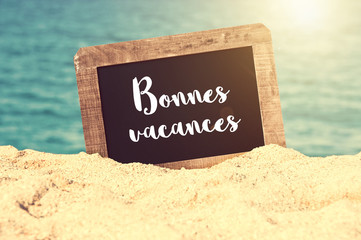 Bonnes vacances (meaning Happy holiday in French) written on a vintage chalkboard in the sand of a beach