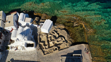 Aerial drone photo of popular landmark chapel of Paraportiani with beautiful emerald colour rocky seascape next to little Venice, main town of Mykonos island, Cyclades, Greece