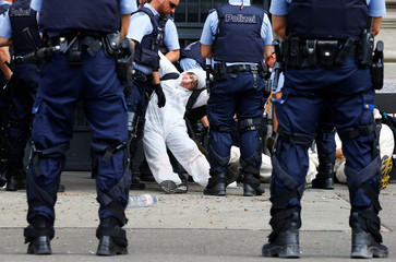 Swiss police officers detain environmental activists blocking the entrance to the headquarters of Swiss bank Credit Suisse in Zurich