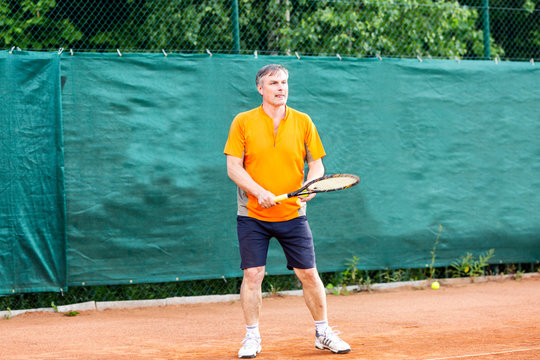 A middle-aged man plays tennis on a court with a natural earth surface on a sunny summer day.