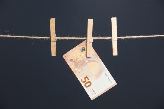Billetes de Euro, colgados de un cordel y unidos por unas pinzas de exstender la ropa. Dinero de curso legal. Materia prima de los bancos para sus finanzas, para dejarlo a ciertos tipos de interés.