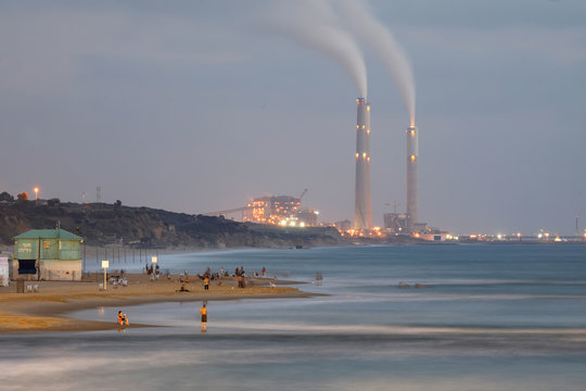 A power station is seen in the background as beachgoers are seen along the shore of the Mediterranean Sea at a beach in Ashkelon, Israel