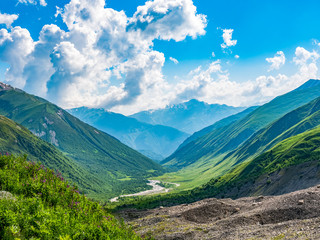 Idyllic landscape with blue sky, fresh green meadows, river and snowcapped mountain top. Svanetia region, Georgia