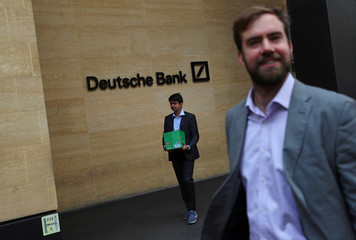 A man carrying a box leaves a Deutsche Bank office in London
