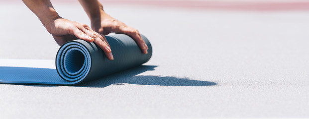 Close-up of a young woman folding blue yoga or fitness mat after working out. keep fit concepts image. copyspace for your individual text.