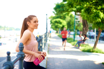 Shot of young woman drinkin protein shake after jogging