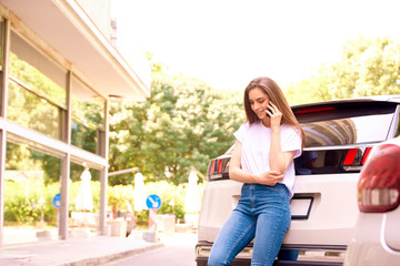 Young woman using her cell phone while standing on the street next to her car