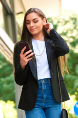 Attractive young woman standing on the street and text messaging