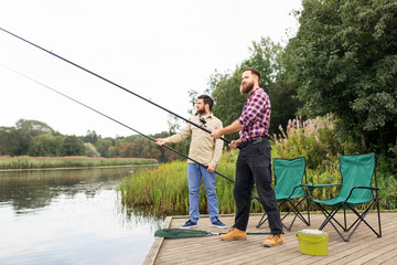 Tuinposter Ontspanning leisure and people concept - male friends with fishing rods on lake pier