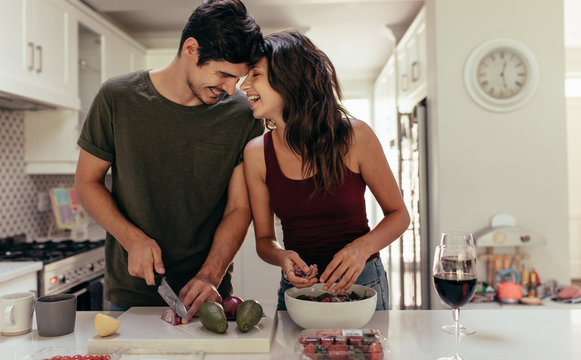 Loving couple cutting vegetables together in kitchen