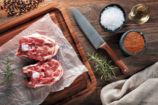 Raw lamb neck meat on white cooking paper and wooden cutting table.
