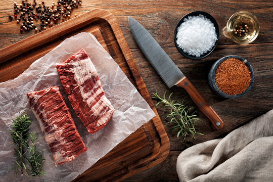 Raw calf skirt steak meat on white cooking paper and wooden cutting table.