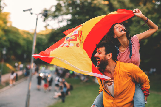 Young couple dancing at a festival with a Spanish national flag