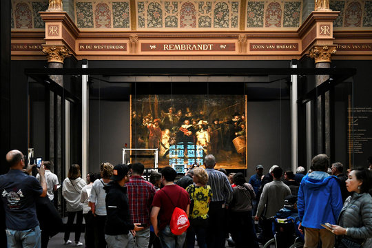 People look at Rembrandt's painting 'The Night Watch', protected by a glass barrier and video surveillance, as it undergoes public restoration after a first phase of study, in Rijksmuseum in Amsterdam