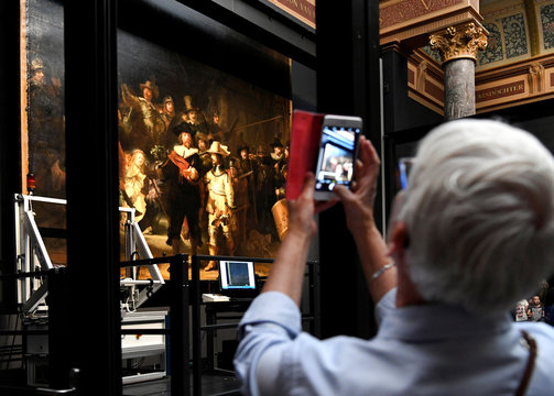 A woman uses her phone to take pictures of Rembrandt's painting 'The Night Watch', protected by a glass barrier and video surveillance, as it undergoes public restoration after a first phase of study, in Rijksmuseum in Amsterdam
