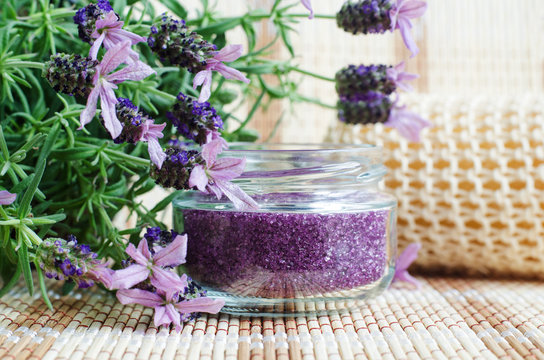 Homemade purple exfoliating scrub (foot soak or bath salt) with essential lavender oil. Topped lavender flowers close up. Natural skin and hair care. DIY beauty treatments and spa recipe. Copy space.