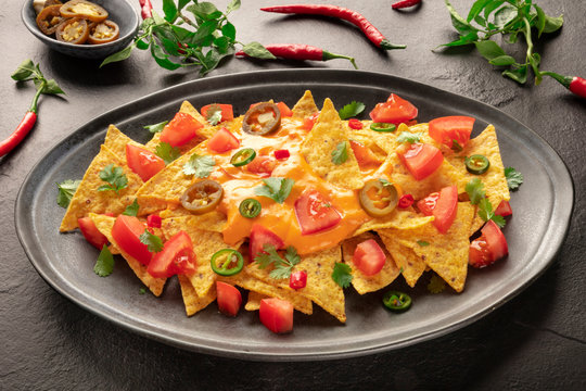 Mexican nachos with a cheese sauce, chili and jalapeno peppers, tomatoes, and cilantro on a black background