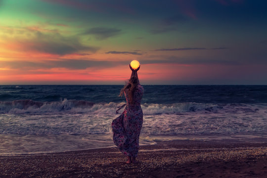 The girl holds the moon in her hands.