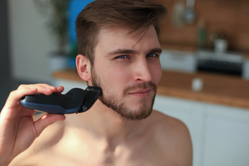 Shaving procedure. Handsome young man shaving his face with electric shaver while standing in front of the mirror.