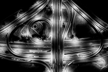 Aerial View Above of Busy Highway Road Junctions at Night. The Intersecting Freeway Road Overpass....
