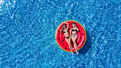Aerial view of young pretty woman lying on inflatable watermelon mattrass floating and relaxing in swimming pool. Summer vocation.