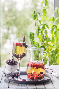 White wine sangria or punch with berries and ice in glass and pincher. Homemade refreshing fruit sangria.