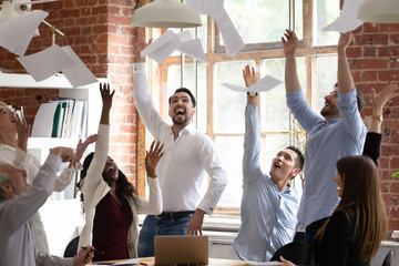 Euphoric diverse business team tossing throwing papers celebrate success victory